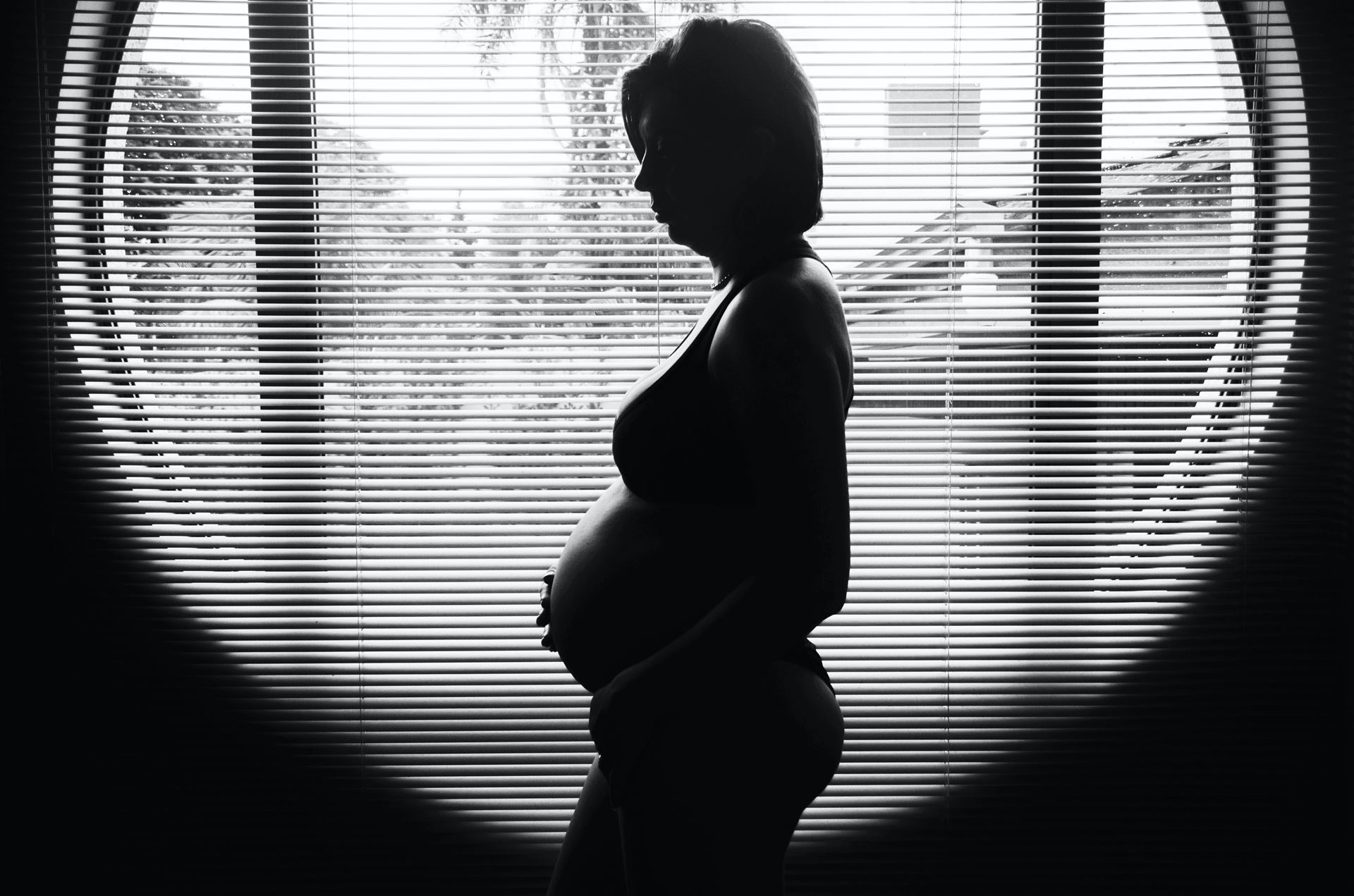 Black and white image of a pregnant individual's silhouette in front of a window with venetian blinds. Photo by Camila Cordeiro on Unsplash