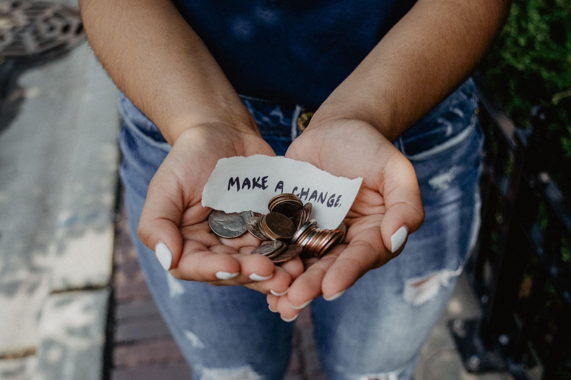 Image of hands holding a pile of a change and a note that says make a change. Photo by Kat Yukawa on Unsplash.